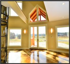 Entrance to the 3-story circular Deltec home. Love the windows above the door and how they echo the shape of the timber frame enytryway!