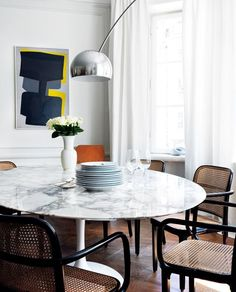 Arco hangs neatly over this marble table in this sunlit modern interior with unique wall art.