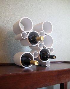 Acredite, este belo apoio para garrafas de vinho foi feito com canos de PVC! Parece simples? Sim, é muito simples! Os pedaços dos canos ganharam furinhos e foram presos internamente por pequenos parafusos e porcas, para aguentarem o peso das garrafas