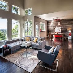 Love how the sleek lines and modern feel of the furniture mixes with natural elements--wooden floor and wall, and outside view.