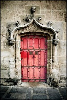ornate stone doorway w/ bright pink weathered door