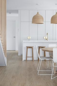 The classic combination of Oak and White is a foolproof formula when looking to create a coastal style home. Add warmth with brass tapware and texture by installing rattan pendant lights. Follow us on Pinterest and Instagram for more design tips. Click the link to head to our website and download free tip sheets, colour schemes, plans and tools #pendantlight #rattanpendant #brasshandles #islandbench #brasstapware #brasstap #timberlooktiles #timbertiles #whitekitchen #pendant #timberbarstool