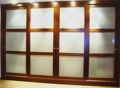 Armario empotrado con puertas de corredera realizadas en madera maciza, con paneles de vidrio lacado.