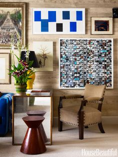 The homeowners' collection of art is hung salon-style in the family room above a mirrored desk, side table, and chair brought from their previous home.