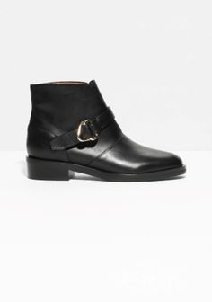 Smooth leather boots that reach an attractive ankle height, featuring a buckle detail across the vamp.