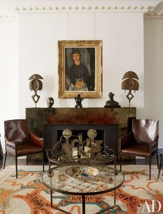 Leather Jean-Michel Frank chairs flank the custom-made mica mantel in a London sitting room by Jacques Grange. The portrait is by Amedeo Modigliani. The serpentine bronze bench is by Claude and François-Xavier Lalanne, and the cocktail table is by Jean Royère. DESIGNER: Jacques Grange PHOTOGRAPHER: Henry Bourne