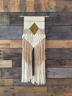 Handmade woven wall art/woven wall hanging in ivory, cream, nude, dark mustard yellow, charcoal, mushroom grey, and with gold elastic detail. Hung on a