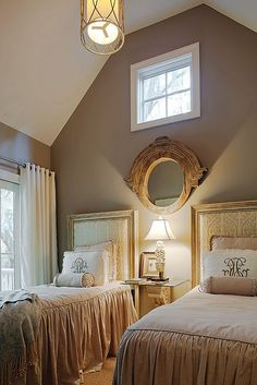"in this guest bedroom the ""mansard mirror is hung above the lamp and between the beds."""