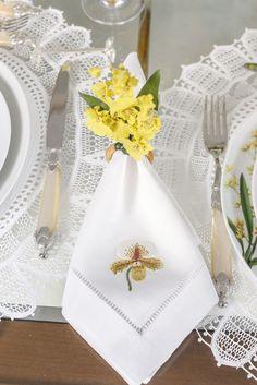 Guardanapos com orquídeas bordadas em linho branco da Matisse Casa com porta-guardanapos de chuva-de-ouro by Couvert em mesa radiante!