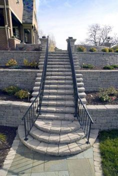 An elegant stairway with a scalloped landing at the bottom bisects this three-tiered wall. VERSA-LOK caps were used for the stair treads.