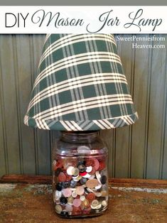 It's simple to turn an old glass mason jar into a fun lamp! Make your own DIY Mason Jar Lamp using old jars and small collectibles, like buttons, spools of thread, blocks...you name it!