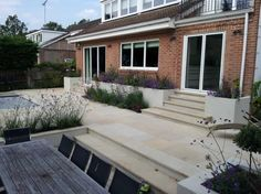 Harvest Sawn Sandstone Paving (HIGH MAINTENANCE) has been used alongside matching step treads in this modern garden by Buffalo Landscapes.