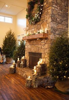 Elegantly primitive this fireplace plays up the natural stack stone with tree trunks acting as candle holders and is accented with multiple lit trees