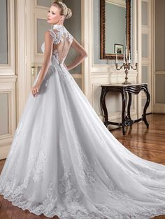 Vestido de noiva rodado, decote princesa, gola alta, tela paetizada com barrado e aplicações de renda, corpo com aplicações de renda bordadas com pedrarias diversas, transparência nude.