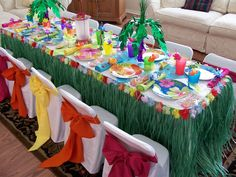 Luau party table...like the grass skirt with flower trim, palm trees are cute