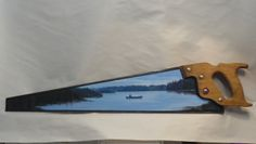 "acrylic on handsaw ""canoe on summit lake"" hangs horizontally by a nail hole on saw edge"