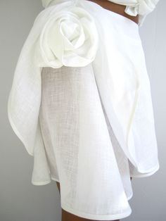 White linen skirt with structured rose on one side.