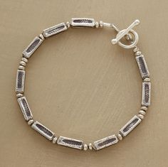 """Slender bars of sterling silver are stamped with a delicate fern leaf design. Handmade in the USA for Sundance. 7""""L."""