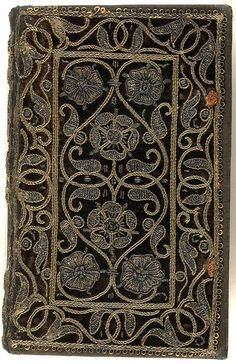 16th century embroidered velvet book with scroll and floral pattern.