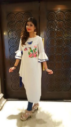 A sweet yet trendy outfit in white linen, sporting a cute hand painted motif.The asymmetrical hemline and smart bell sleeves add a touch of trendy elegance. Kurti Sleeves Design, Sleeves Designs For Dresses, Dress Neck Designs, Sleeve Designs, Blouse Designs, Kurti Patterns, Dress Patterns, Stylish Dresses, Fashion Dresses