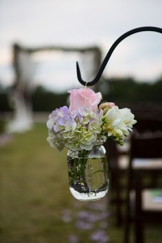 Hydrangea, rose, and freesia hung on shepherd's hooks as wedding ceremony aisle markers {Shelly Taylor Photography}