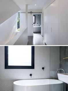 At the top of the stairs in this modern house is a bathroom that's hidden behind a white sliding barn door. The bathroom features a freestanding bathtub with rain shower, an accent wall of penny tiles and matte black accents that match the black window frame. #ModernBathroom #PennyTiles #BathroomIdeas #InteriorDesign #SlidingBarnDoor