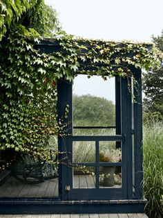 Beach grass surrounds a small screened-in porch at the back of the house.