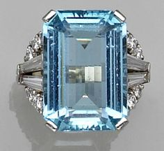 An aquamarine, diamond and platinum ring, circa 1950 the rectangular-shaped aquamarine with openwork round brilliant and baguette-cut diamond shoulders and completed by a fluted hoop; aquamarine weighing an estimated: 15.00 carats; estimated total diamond weight: 1.00 carats