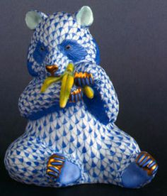 Herend Porcelain Figurine of Panda Bear Eating a Banana. Bear is White and Blue with Blue Fishnet Design, Yellow Banana, and Gold Accents.