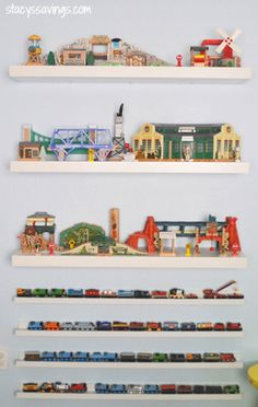 """Keep trains """"on track"""" atop picture ledges, and store larger accessories, like stations, bridges and water towers, on floating shelves. Pro tip: This works for other wheeled toys, as well, such as tiny cars and finger skateboards. Click through for more on this and other toy organization ideas."""
