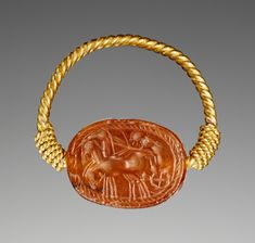 Scarab with a Three-Horse Chariot and Driver; Unknown; Etruria; 400–300 B.C.; Carnelian and gold; 0.8 × 1.5 × 1.2 cm (5/16 × 9/16 × 7/16 in.); 81.AN.76.161; J. Paul Getty Museum, Los Angeles, California