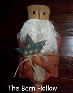 Americana Santa. He is made of painted and grunge stained muslin and is approximately 15 tall and 5 wide. His body is attached to a vintage wood