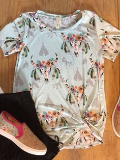 FLORAL BULL PRINT TUNIC TOP WITH KNOTTED HEM.  95%POLYESTER 5%SPANDEX  MADE IN USA  SMALL 2-4  MEDIUM 6-8  LARGE 10-12  XLARGE 14-16  2X 18-20  3X 22-24
