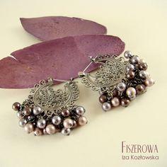 FISZEROWA - Perłowa secesja == Urocze, bardzo retro kolczyki wykonane z ażurowych srebrnych baz w króte wpleciono szklane perły Swarovskiego. Dla podkreślenia charakteru kolczyków zostały zoksydowane i wypolerowane.  Długość kolczyków: 3,2 cm. Szerokość kolczyków: 3,2 cm.