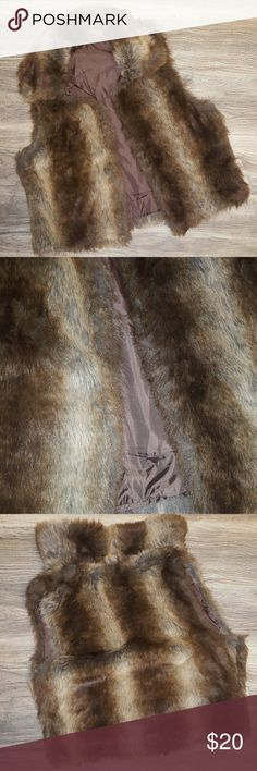 Faux fur vest tan and brown Beautiful faux fur vest, lined on inside, brown and tan.   No size or label, fits like a large.  Refer to measurements   Laying flat and closed measures approximately 17 inches across bust, 24 inches from shoulder bottom hem.  Arm opening measures 11 inches. Jackets & Coats Vests
