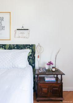 Quarto de casal tem paredes com quadros e objetos e cabeceira forrada com tecido.