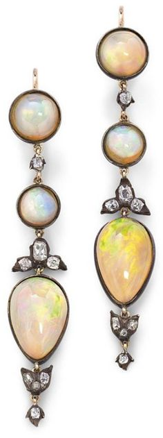 A pair of opal and diamond ear pendants. Each designed as a graduating line of variously-shaped cabochon opal between old brilliant-cut diamond spacers, length 6.3 cm, total opal weight approximately...