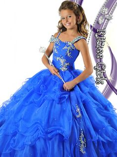 The Ritzee girls pageant gown 6464 is a spectacular little girl beauty dress with a different one shoulder neckline adorned with hand sewn A.B. rhinestones that trail down into the bodice that sits on top of a ruffled organza skirt with chunky rhinestone beaded appliques.