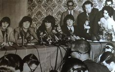 Tony Barrow (holding microphone) with Brian Epstein (in sunglasses) and the Beatles