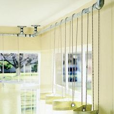 """The hardware store yielded the chains and 1/2-inch galvanized-steel conduit pipe used to hang these draperies. Elbow connectors allow the 90-degree turn needed to drop the """"rods"""" from mounting plates screwed into anchors in the ceiling"""