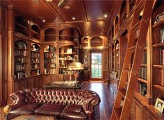 "This handsome library is a multi-purpose room that serves as his ""man-cave"".  It features a personal living area with a fireplace, floor to ceiling library shelving, space for your desk and even a concealed laptop station."