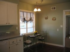 Kitchen after remodel.  Dark brown wood laminate flooring make the white cabinets pop, along with the manatee green paint, a very grayish green.  After the flooring, new white trim was put throughout the house.