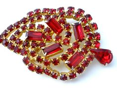 Vintage High End Costume Jewelry - This is a beautiful gold tone leaf brooch with prong set ruby red rhinestones. This pin has emerald cut, round and a pear shaped rhinestones. It measures 2.63 inches