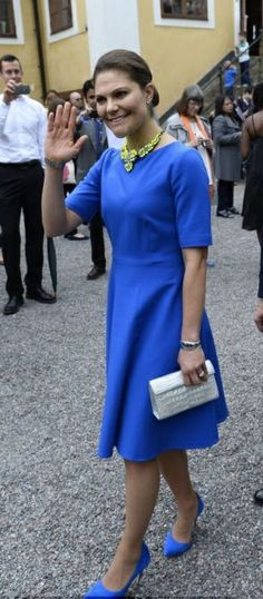 Swedish Crown Princess Victoria wearing an elegant electric blue dress with matching blue suede court shoes and an elaborate gold necklace, her hair was pulled back into a tight bun.