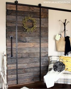 upcycled barn door using broken scooter wheels for hanging hardware - AKA Design