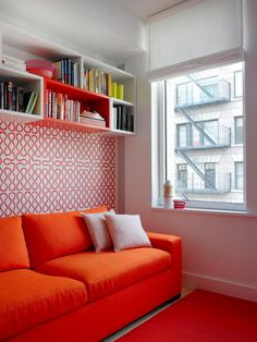 A little color and pattern go a long way in a small space. Here, graphic wallpaper and modular bookshelves complement the sofa's vibrant hue and color the room a funky retreat.