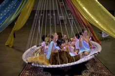 Children love rocking in a Floating, Hanging Bed. Shown here with colorful fabric decor.