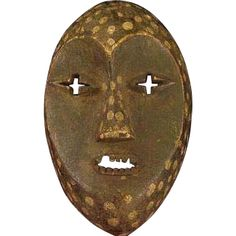 Rare Lega Mask, DRC  An interesting anthropomorphic mask showing generations of use.  Recognizable heart shaped face. Wide eyebrows connecting to the nose.  Wonderful patterned spots created by the application of kaolin suggests a reference to the leopard, and while the facial features are anthropomorphic, a monkey-like resemblance is also present. The slightly open mouth bears small wooden teeth.