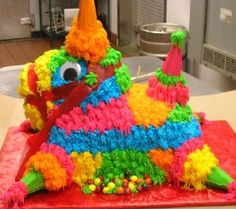 3D Pinata Cake - Fr. Vanilla cake shaped and carved to look like a donkey/horse. the ears, legs and tail are ice cream cones filled with Skittles candy with a skewer royal iced to the bottom of the cone to secure it. Then I took a cookie and royal iced it to the cone to keep the candy from falling out, then stuck the skewers into the cake and decorated it. SO the child receiving the cake just had to hit and break the cones to make the candy come out. The nose strap is fruit by the foot…
