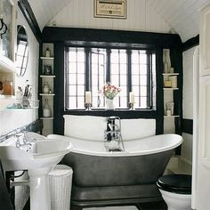 black & white bathroom-shelving by the windows is good use of space